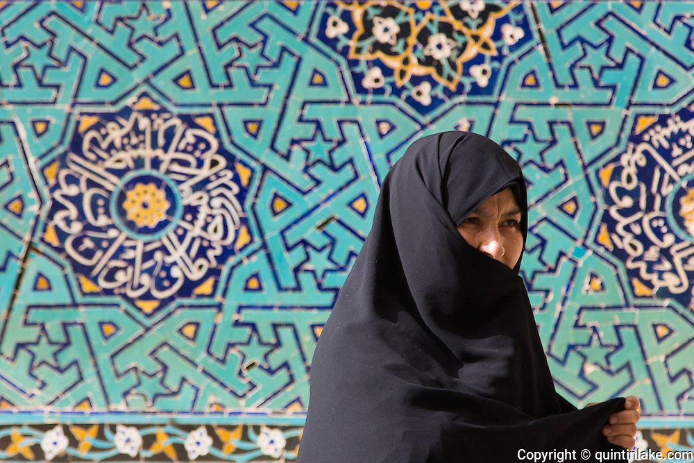 A woman wearing a chador walks past the blue tile work of the the J?meh Mosque of Yazd, Iran