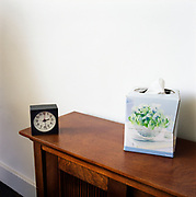A box of tissue and a small clock on a narrow wooden side table, in a psychologists' office in Soho.