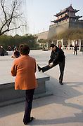 People stretching before practising Tai chi as part of their morning exercise, in the park by the City Wall, Xian, China