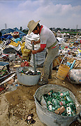 CIUDAD NEZAHUALCOYOTL, DF, MEXICO: A man smashes bottles before recycling the glass in the Ciudad Nezahualcoyotl dump on the edge of Mexico City, Sept. 23, 1993. Hundreds of people live in the dump and make a living by scavenging through the refuse brought to the dump by Mexico City's garbage trucks.  PHOTO ©  JACK KURTZ   POVERTY  HOMELESS  ECONOMY   SOCIAL ISSUES   LABOUR