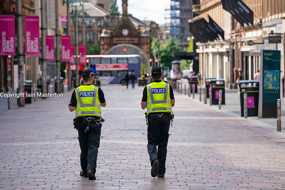 Glasgow, Scotland, UK. 6 June 2020. Normally busy shopping district of Buchanan Street in Glasgow city centre is almost deserted on a Saturday lunchtime. Shops and businesses remain closed and in many cases boarded up.  Police patrol empty Buchanan Street pedestrian street. Iain Masterton/Alamy Live News