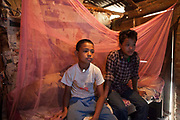 Two Nepalese brothers sit on their bed and watch television in their bedroom at home in Kathmandu, Nepal.  Their home is made from bricks and wood with a corrugated iron roof.  The older boy used live and beg on the streets, but has been reunited with his family through Voice of Children organisation.