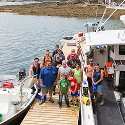 Jim Merryman (center - gray shirt)  of Potts Harbor Lobster with several of his employees and fisherman who supply his business with lobster. Harpswell, Maine.