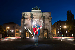 Young man drawing with light a heart shape in the night in front of victory gate in Munich, Bavaria, Germany