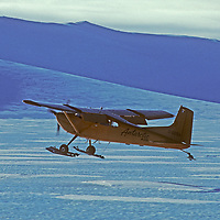 With (the late) pioneering Antarctic pilot Giles Kershaw at the stick, a Cessna 185 ski plane takes off from a bare ice glacier at Patriot Hills in the Southern Ellsworth Mountains, Antarctica.