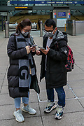 March 14, 2020, London, England, United Kingdom: People wearing face masks standing in front of Canary Wharf underground station in London, Saturday, March 14, 2020. For most people, the new COVID-19 coronavirus causes only mild or moderate symptoms, such as fever and cough. For some, especially older adults and people with existing health problems, it can cause more severe illness, including pneumonia. (Credit Image: © Vedat Xhymshiti/ZUMA Wire)