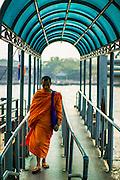 22 JANUARY 2013 - BANGKOK, THAILAND: A Buddhist monk walks to shore after getting off a ferry at Saphan Phut Pier along the Chao Phraya River.       PHOTO BY JACK KURTZ