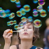 Girl blows soap bubbles during a soap bubble day in a public park in Budapest, Hungary on August 25, 2013. ATTILA VOLGYI
