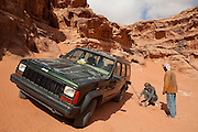 Bedouin men siphon gasoline from a jeep in the desert in Wadi Rum, Jordan.