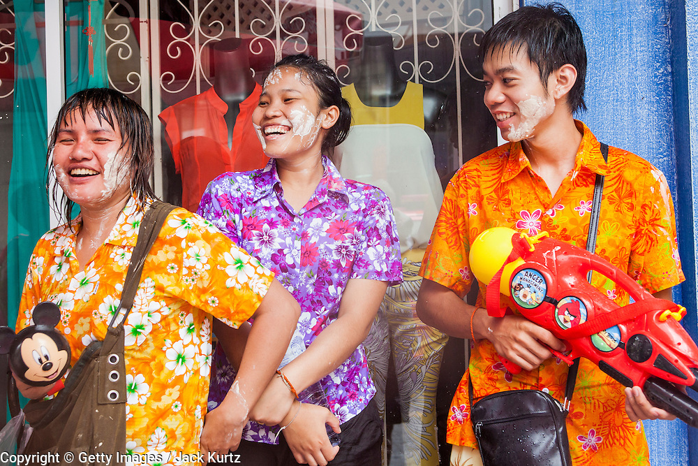 14 APRIL 2013 - BANGKOK, THAILAND:  People in a water fight take shelter under a store awning on Soi Convent on April 14, 2013 in Bangkok, Thailand. The Songkran festival is celebrated in Thailand as the traditional New Year's Day from 13 to 15 April. The throwing of water originated as a way to pay respect to people and is meant as a symbol of washing all of the bad away. PHOTO BY JACK KURTZ