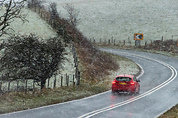 © Licensed to London News Pictures. 05/12/2020. Llanfihangel Nant Melan, Powys, Wales, UK. Cars drive along the A44 in wintry conditions near Llanfihangel Nant Melan in Powys, UK. Photo credit: Graham M. Lawrence/LNP