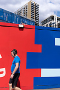A Londoner walks beneath new housing and the construction hoarding that surrounds the Elephant & Castle shopping centre that is currently undergoing demolition, seen from the Walworth Road in Southwark,  on 27th May 2021, in London, England.