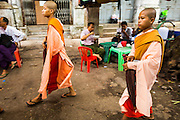04 JUNE 2014 - YANGON, YANGON REGION, MYANMAR: Buddhist nuns walk down Merchant Street in Yangon, Myanmar (Rangoon, Burma). Yangon, with a population of over five million, continues to be the country's largest city and the most important commercial center.     PHOTO BY JACK KURTZ