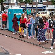 NLD/Amsterdam/20190803 - Gaypride 2019, lange rij mensen voor een diksy om te plassen