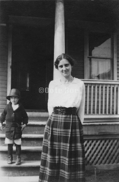 A young mother and child standing outside there house