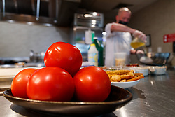 Ripe tomatoes and Chef, Atico, Fort Worth, Texas, USA. Atico is a Spanish tapas bar atop a Stockyards hotel and is owned by Tim Love.
