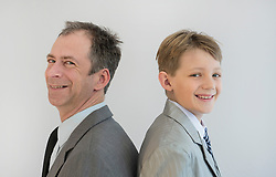 Portrait of father and son smiling, close up