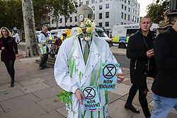 London, UK. 13 October, 2019. A climate activist from Extinction Rebellion, wearing a gas mask draped with flowers, protests outside New Scotland Yard.