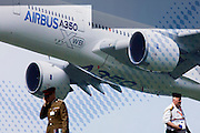 Foreign military officers pass beneath a large billboard of the Airbus A350 XWB on the side of the Airbus corporate chalet at the Farnborough Air Show, England. The A350 XWB is the only all-new aircraft in the 300-400 seat category. The A350 XWB is a family of long-range, two-engined wide-body jet airliners developed by European aircraft manufacturer Airbus. The A350 is the first Airbus with both fuselage and wing structures made primarily of carbon-fiber-reinforced polymer. It's scheduled to enter commercial service later in 2014.