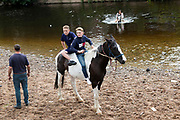 Two boys on horseback beside the River Eden at Appleby Horse Fair, the biggest gathering of Gypsies and travellers in Europe, on 14th August, 2021 in Appleby, United Kingdom. Appleby Horse Fair attracts thousands from Gypsy, Romany, and traveller communities annually, making it the biggest gathering of its kind in Europe. Generally held for a week every June, the fair was postponed in 2020 and pushed forward to August in 2021 due to Coronavirus.