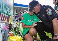 A makeshift memorial grows in front of the B-quick store on Airline in Baton Rouge where officers were killed on Sunday.<br /> Woman who stopped to pay respects at the makeshift memorial is comforted by Chaplain Bob Ossler from New Jersey, who also went to Dallas to comfort people following the police shooting there.
