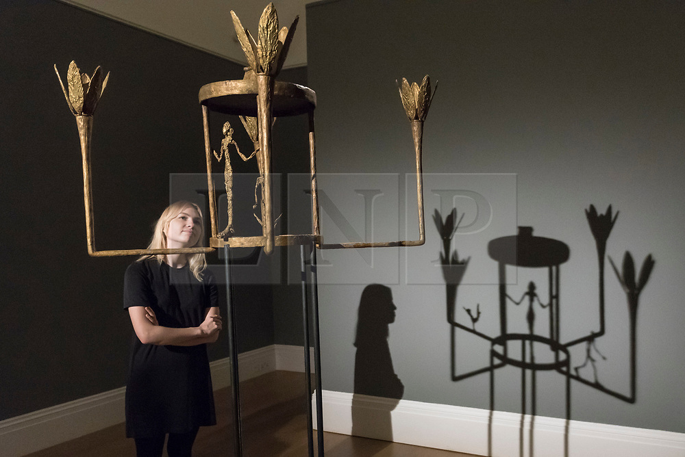 © Licensed to London News Pictures. 22/02/2018. LONDON, UK. A staff member stands with ''Lustre Avec Femme, Homme Et Oiseau'' by Alberto Giacometti, (Est. £6,000,000 - 8,000,000)at the preview of Sotheby's upcoming Impressionist, Modern & Surrealist Art auctions taking place at Sotheby's, New Bond Street, on 28 February. Photo credit: Stephen Chung/LNP
