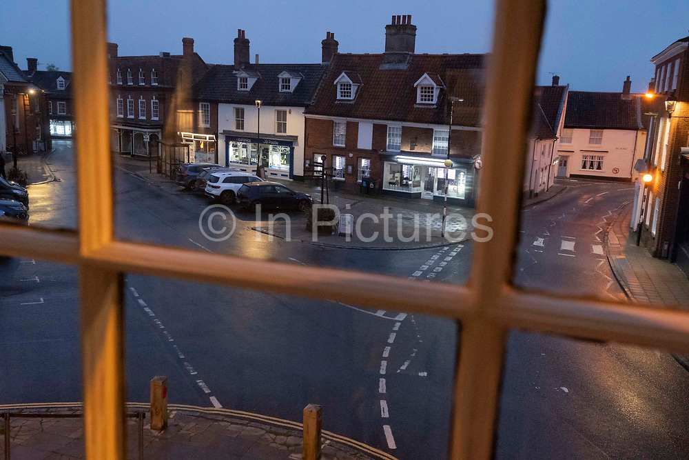 An evening viewpoint through a sash window of the road junction in a market place of a rural Norfolk town, on 30th June 2021, in Aylsham, Norfolk, England.