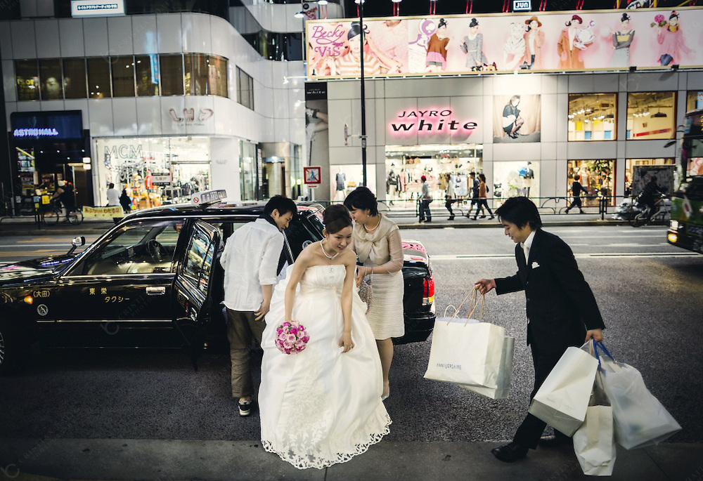 A woman in wedding dress and groom in suit buying in Meiji Dori in Shibuya at night. With 15 square kilometer and a resident population of more than 200000 people it has become one of the best shopping districts of the city specially for young people. It has also a lively nightlife and the streets are busy until late at night.