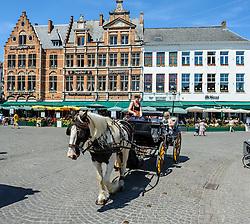 Horse drawn carriage carrying tourists in Grote Markt, Bruges, Belgium<br /> <br /> (c) Andrew Wilson | Edinburgh Elite media