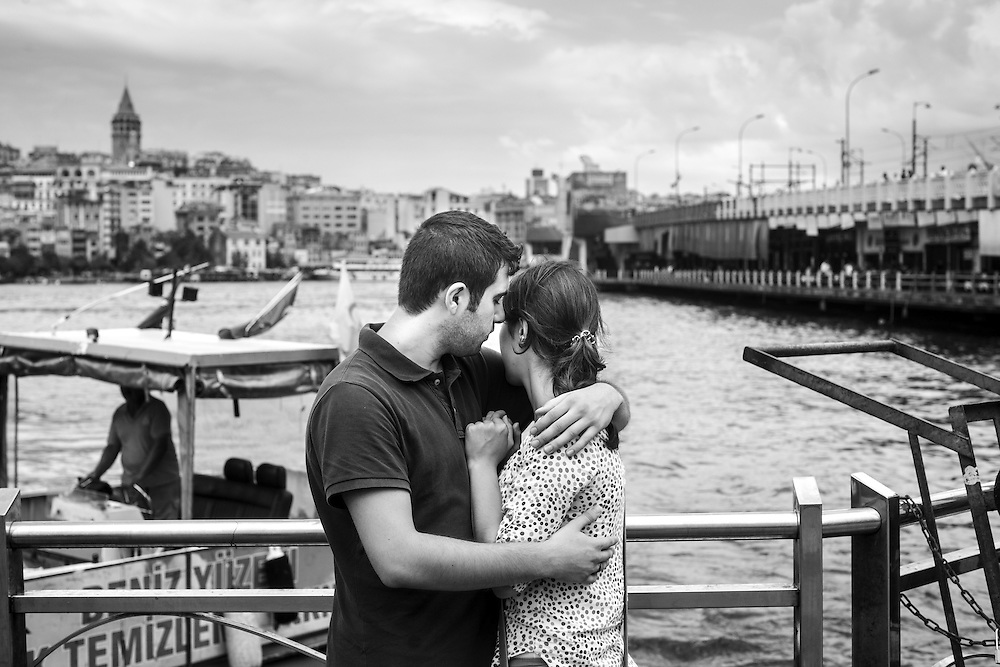 A couple embraces near Galata bridge in Istanbul.