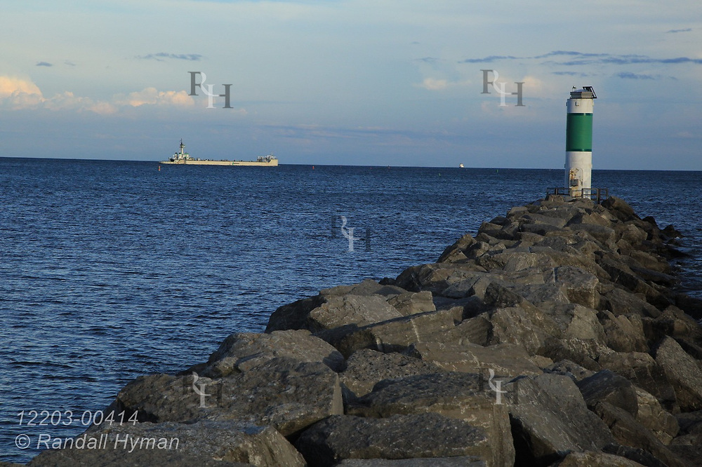 Breakwater and lighthouse frame distant freighter on Lake Huron on a September afternoon  in Alpena, Michigan.