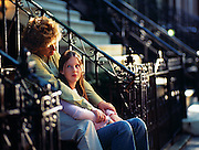 A woman and her young daughter have a talk outside of their Brooklyn, New York brownstone home