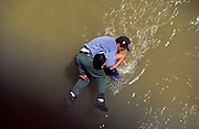 "EL PASO, TEXAS, USA: A ""coyote"" or guide, carries an undocumented immigrant from Ciudad Juarez, Chihuahua, Mexico, across the Rio Grande River to El Paso, Texas.  PHOTO © JACK KURTZ  BORDER   IMMIGRANTS  WATER  TRAFFICKING"