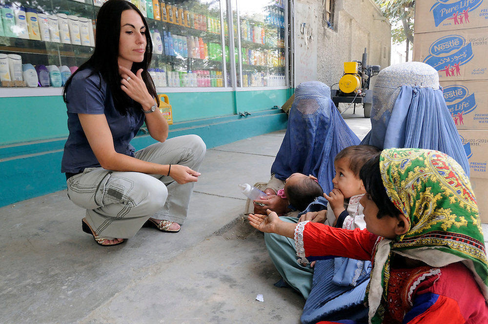 """Pilot, Danielle Aitchison, stops to give money to women and children outside a grocery story in Kabul.  She said, """"You come out and you feel sorry for them.  They have to reduce themselves to being on the street with their children.  You know that probably their husbands have been killed, so it does tug on your heart.""""   ..Danielle flies in Afghanistan for The United Nations Humanitarian Air Service (UNHAS).   ..."""