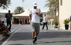 Mercedes driver Lewis Hamilton arrives at the circuit during practice at Yas Marina Circuit, Abu Dhabi.