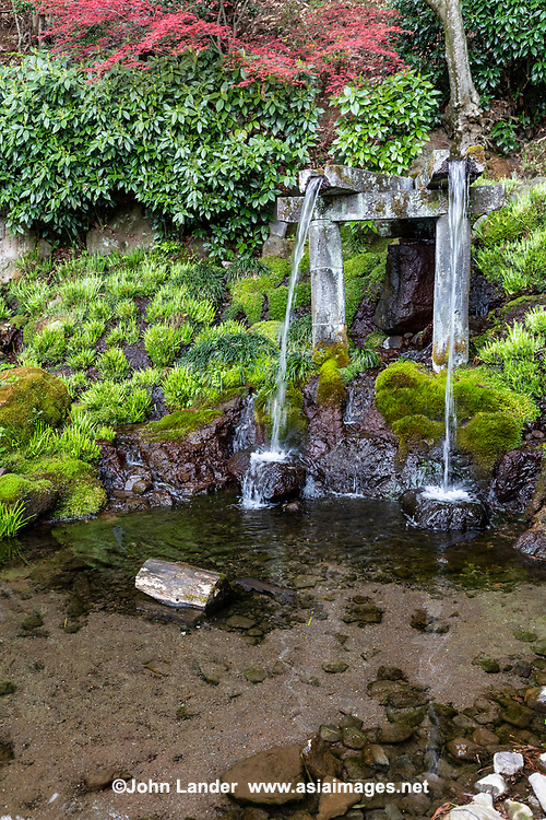 Jizo-ji Temple Garden Waterfall -Jizo-ji Temple Garden belongs to the Soto Zen sect of Buddhism. There is garden of kaiyu shiki teien style of the early Edo period.  Here, the backdrop and borrowed scenery have been used skillfully. Its unique Y shaped waterfall, is an unusual addition.  There is an stone bridge the crosses over the pond, festooned with iris in season while tiny islands appear to be afloat within the pond.  The garden at Jizo-ji Temple is almost hidden and takes some effort to find it behind the main hall.  Seeking it out is well worth the effort.