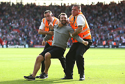 19 August 2017 - Premier League Football - Southampton v West Ham United - A pitch invader grins as he is wrestled off the pitch by two stewards - Photo: Charlotte Wilson