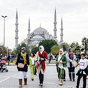 Tourists in Sultanahment Park with the Blue Mosque in the background.