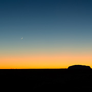 Silhouette of Uluru with clear sky and crescent moon at sunrise