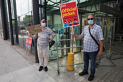 Members of the Public and Commercial Services (PCS) trade union stand on the picket line outside the Department for Business, Energy and Industrial Strategy (BEIS) on the second day of a 3-day strike by workers employed there by the outsourced contractor ISS on 20th July 2021 in London, United Kingdom. The striking cleaners, security guards and other support staff are demanding an end to low pay, improved working conditions, bonuses for having worked through lockdown, annual leave from last year and a Covid return-to-work protocol.