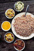 Typical meal in Bhutan: red rice, chilies with potatoes, eggs, cheese. The Namgay household owns and rents land scattered in terraced strips through the hillsides near their home, each strip being devoted to one crop: wheat, rice, chilies, or potatoes. Shingkhey, Bhutan. Published in Material World: A Global Family Portrait, Meals of the World page 177. From Peter Menzel's Material World Project.