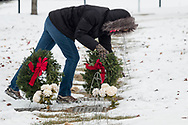Goshen, New York - A woman places a wreath at a graves during a Wreaths Across America ceremony at Orange County Veterans Memorial Cemetery on Dec. 16, 2017. About 3,000 wreaths were placed at graves, and small American flags were added to the wreaths at veterans' graves.