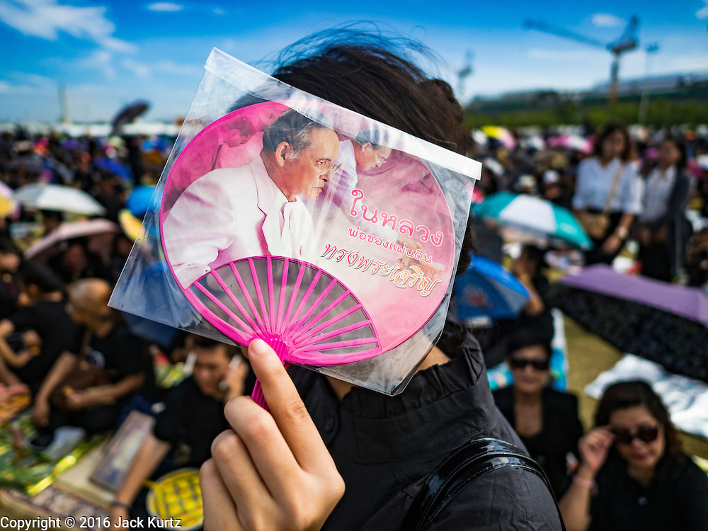 22 OCTOBER 2016 - BANGKOK, THAILAND:  A mourner carries a small paper fan with a portrait of Bhumibol Adulyadej, the King of Thailand, during mourning services at Sanam Luang. Sanam Luang, the Royal Ceremonial Ground, was packed Saturday with more than 100,000 people mourning the Monarch's death. The King died Oct. 13, 2016. He was 88. His death came after a period of failing health. Bhumibol Adulyadej was born in Cambridge, MA, on 5 December 1927. He was the ninth monarch of Thailand from the Chakri Dynasty and is also known as Rama IX. He became King on June 9, 1946 and served as King of Thailand for 70 years, 126 days. He was, at the time of his death, the world's longest-serving head of state and the longest-reigning monarch in Thai history.      PHOTO BY JACK KURTZ