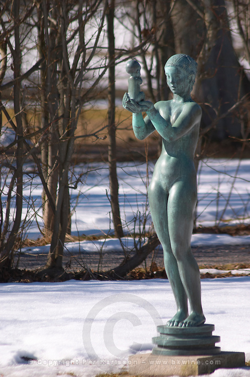A sculpture of a mother and child in the park of the palace Ulriksdals Slottspark in snow in winter. Naked Woman holding a small child in her uplifted hands.