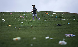 © Licensed to London News Pictures. 05/04/2021. London, UK. A man jogs through litter strewn across the hillside of Primrose Hill in north London, the morning after revellers took to the picturesque location to enjoy the warm spring weather. A relaxation of some lockdown restrictions has gathered larger crowds in many outdoor spaces. Photo credit: Ben Cawthra/LNP