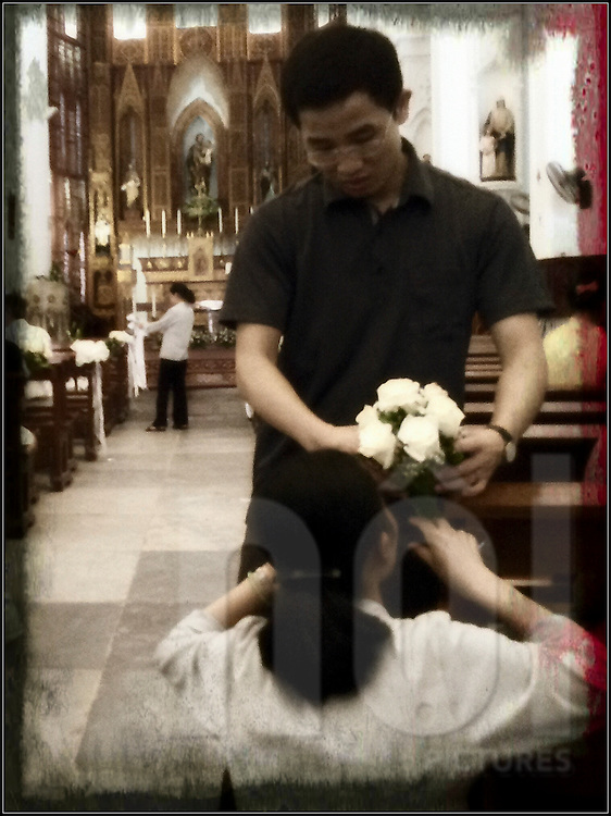 A man gives flowers to a woman in St Joseph Cathedral, Hanoi, Vietnam, Southeast Asia
