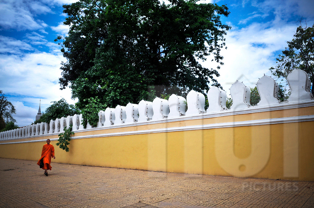 Buddhist monk walks along the Royal Palace in Phnom Penh, Cambodia, Southeast Asia