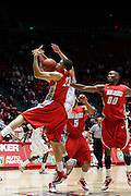 New Mexico guard Phillip McDonald (23) attempts to grab a rebound as his teammates Dairese Gary (5) and A.J. Hardeman (00) look on during an NCAA college basketball game against Utah, Wednesday, Jan. 19, 2011, in Salt Lake City. (AP Photo/Colin E Braley)