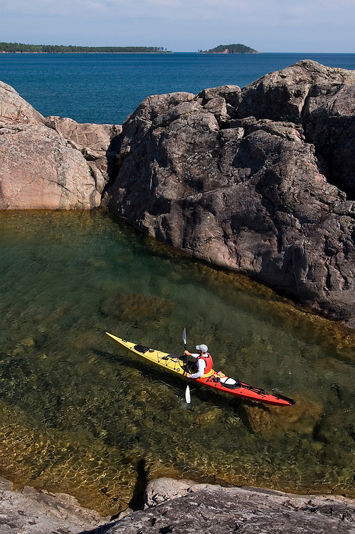 A sea kayaker explores a protected cove with rock walls on Lake Superior while paddling near Marquette Michigan.