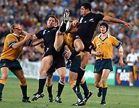 Photo. Steve Holland.Australia v New Zealand, Semi-final at the Telstra Stadium, Sydney. RWC 2003.<br />15/11/2003.<br />Mils Muliaina, left and Leon Mac Donald jump for the ball